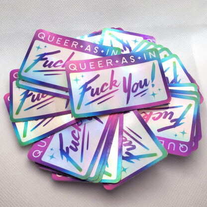 """pile of stickers. Stickers are rectangular with a rainbow border. Text on the sticker reads """"Queer as in fuck you"""""""