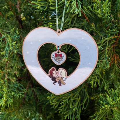 Ornament is heart-shaped, with a heart-shaped cutout in the middle. Chibi versions of Aziraphale and Crowley sit on the inner border of the heart, smooching. the background of the heart is a cloud on the bottom with a grey-blue sky above, snowflakes scattered about. a smaller heart dangles above them, with mistletoe on it.