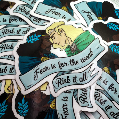 """a sticker printed on white vinyl with Patroclus and Achilles as they appear in the game Hades. Their foreheads are touching and their eyes are closed; both are smiling. A banner wrapped underneath and around them reads """"Fear is for the weak. Risk it all."""""""