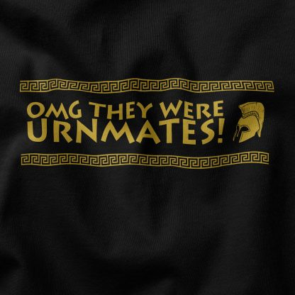 """a black t-shirt. """"OMG they were urnmates!"""" is written across the chest in an ancient Greek-inspired font. Next to the text is a drawing of an ancient Greek helmet typically associated with the hero Achilles. Above and below the main design are borders inspired by Greek design. Everything is colored gold."""
